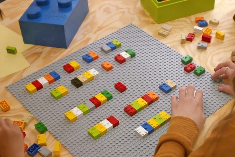 Children laying out lego bricks, designed for educational purposes, to make words in Braille
